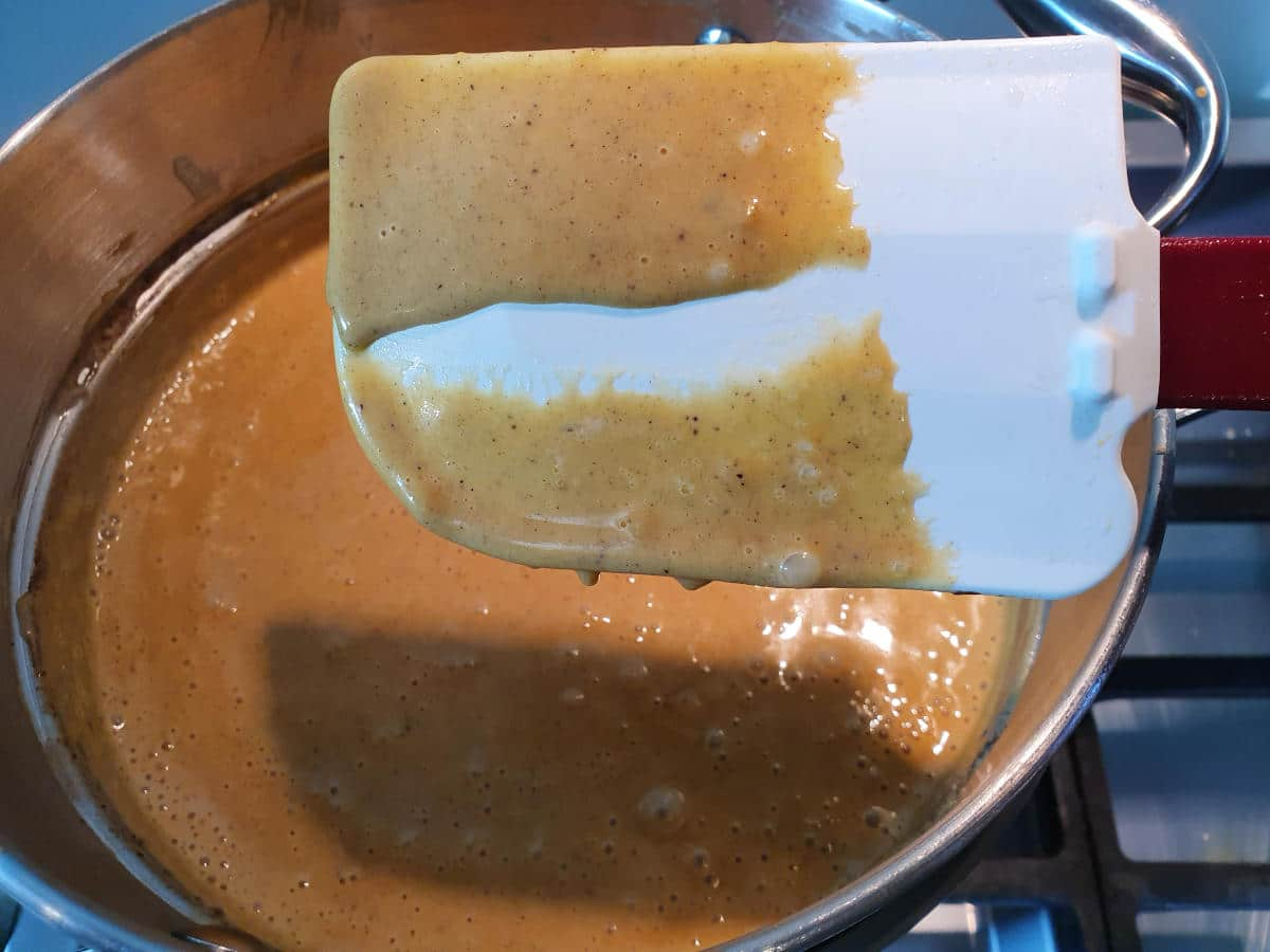 Spatular showing line in custard which indicates its done, held over double boiler with pumpkin spice mix, on a gas stove.
