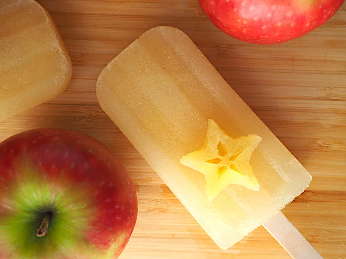 Single mulled apple cider popsicle with apple star on top and apples, on a chopping board.