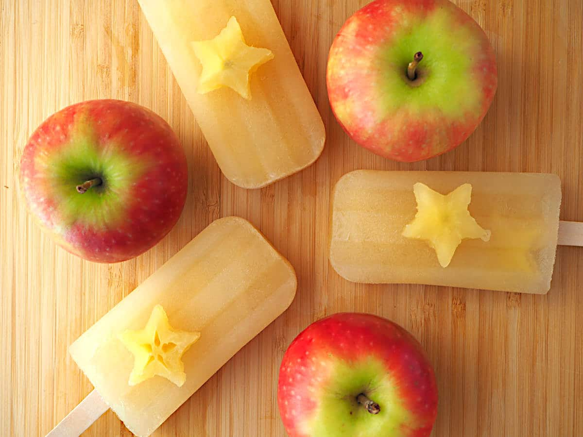 Three mulled apple cider popsicles in a trio all pointing in, with apple stars on top and apples in between, on a chopping board.