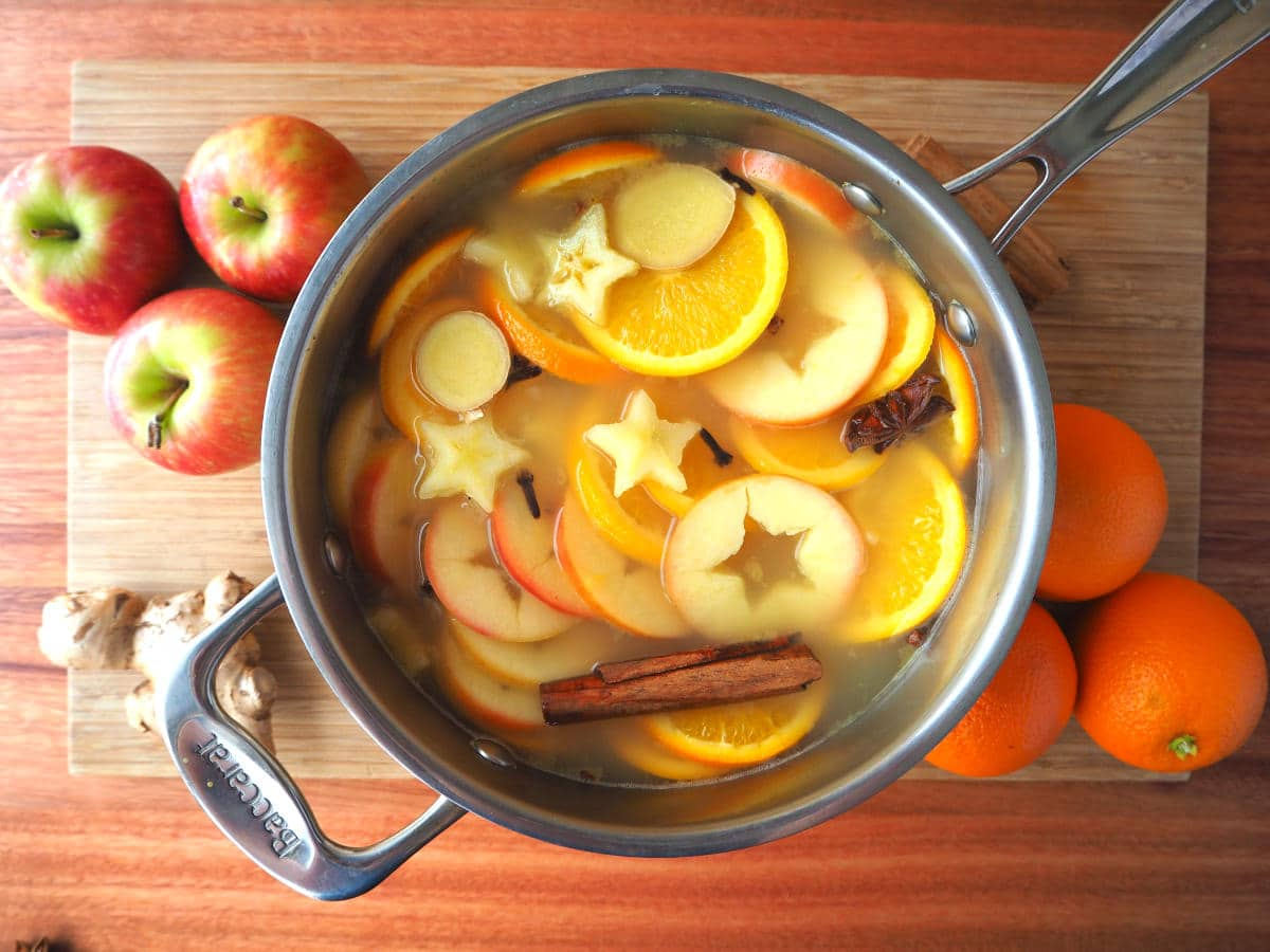 top down view of pot of mulled apple cider on a chopping board, with apples, oranges and ginger root on the side.