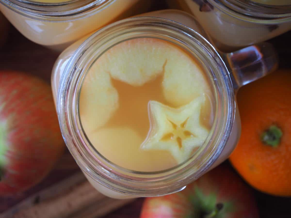 close up top down view of mulled apple cider showing star shapes, with apples, oranges and spices on the side.