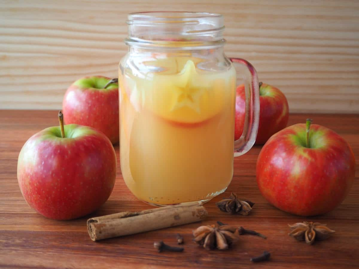 side view of a mason jar mug filled with mulled apple cider, with apples and spices on the side, on a brown board with a light brown background.