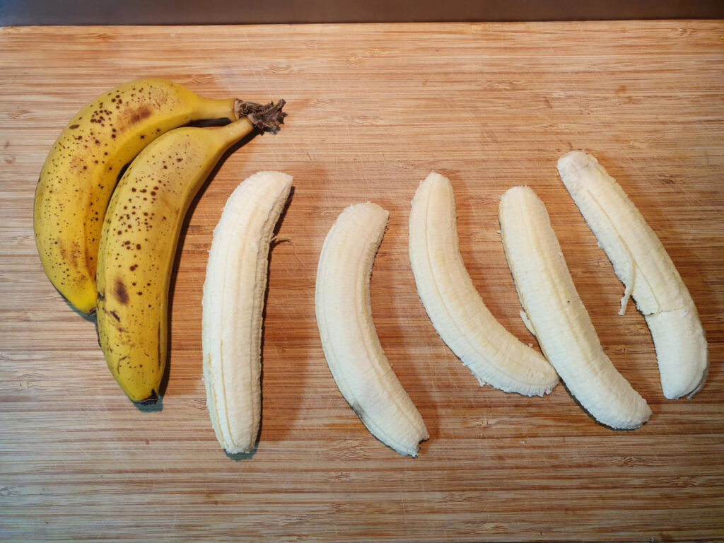 top down view peeling and slicing banana length wise.