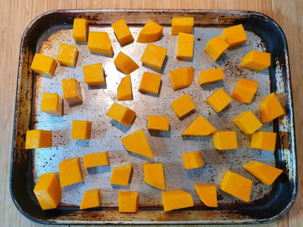 top down view of raw pumpkin on a baking tray, on a chopping board.