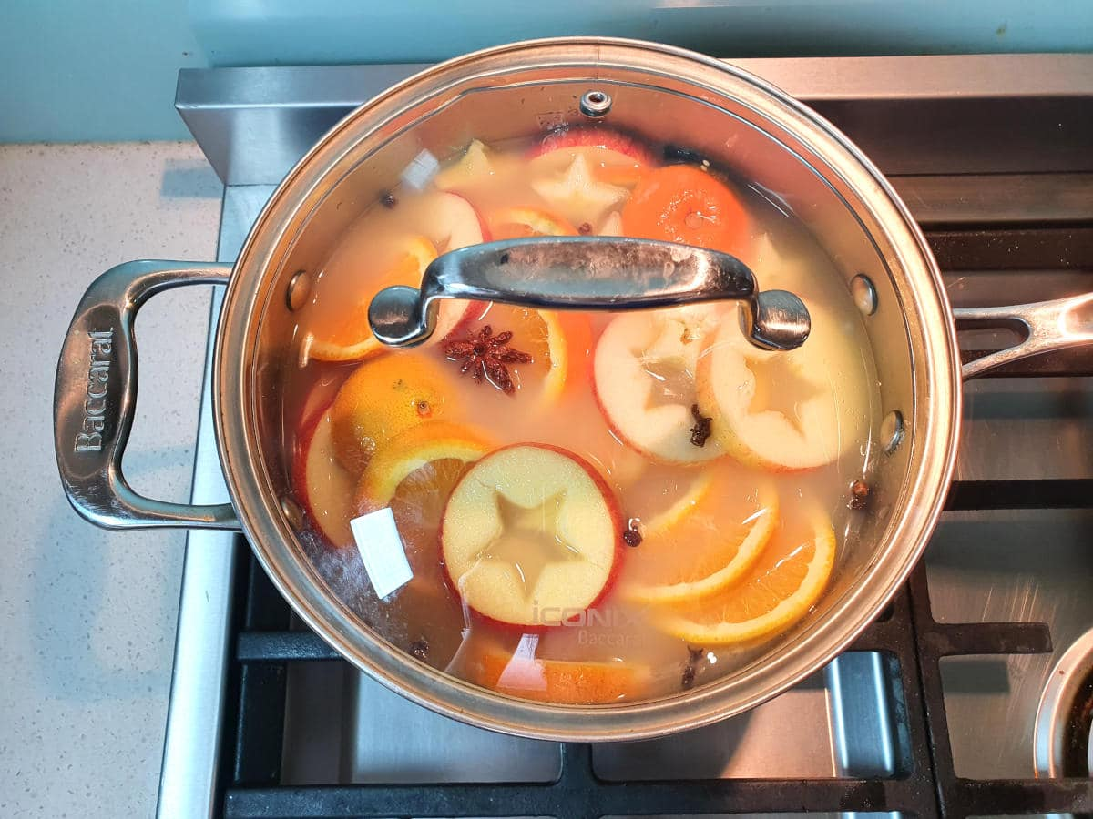 simmering apple cider in pot with lid on.