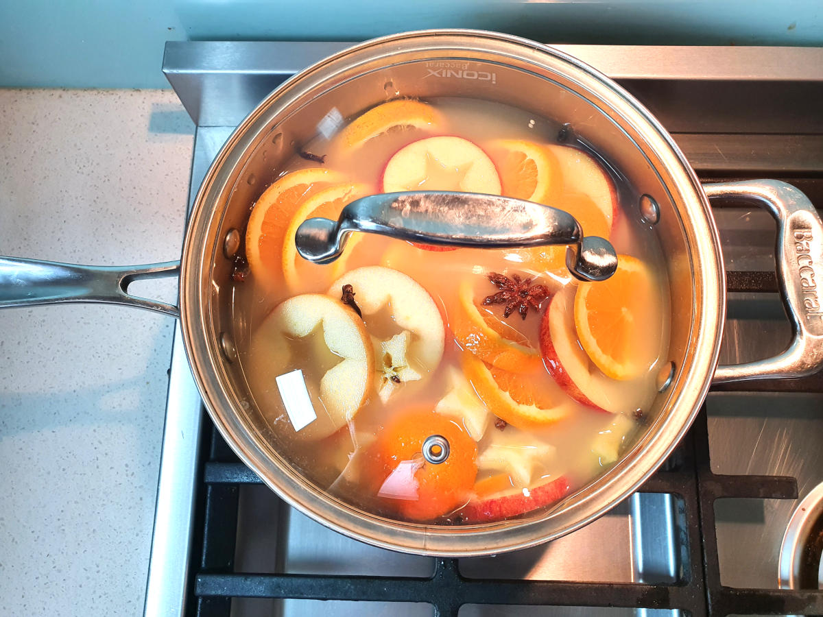 mulled apple cider with simmering in pot with clear glass lid, on a gas stove.