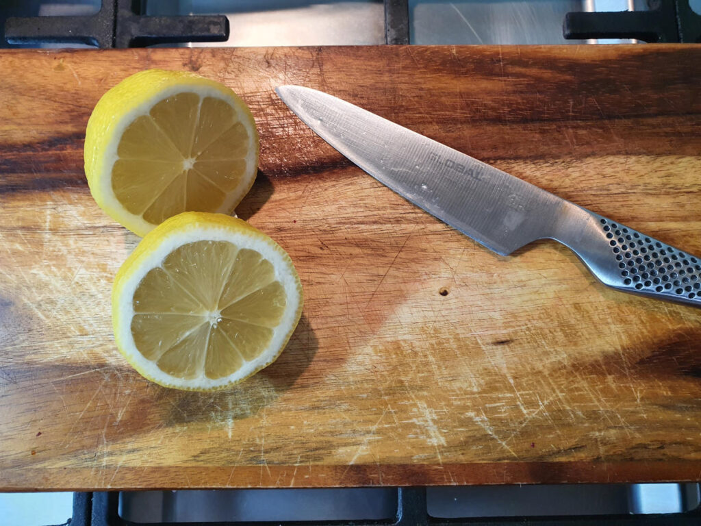 slicing lemons on a chopping board ready to juice.