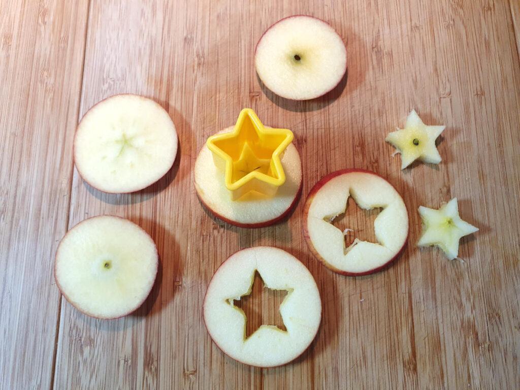 slicing up apples and cutting out small apple stars using a star cookie cutter.