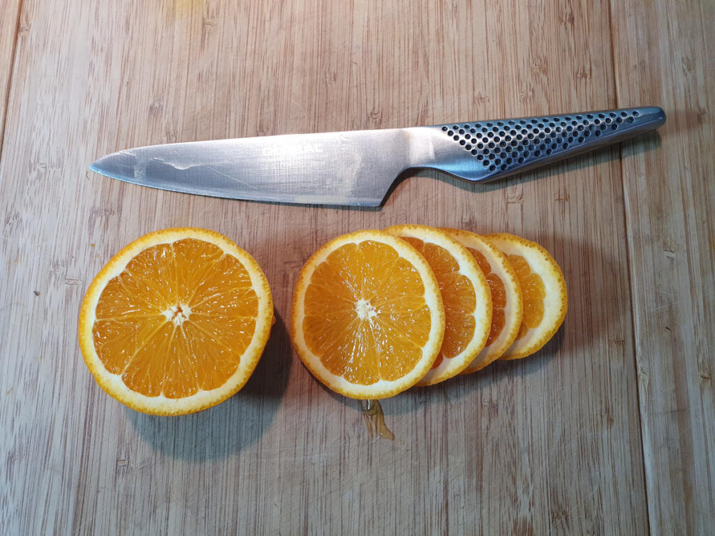 slicing up orange into rounds.