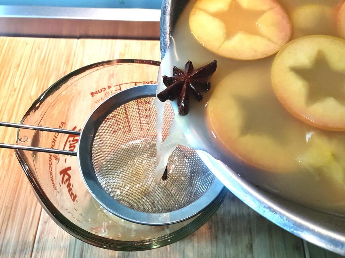 straining cooled apple cider through a sieve into a heat proof jug.