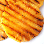 Close up top down view of grilled pineapple showing griddle lines.