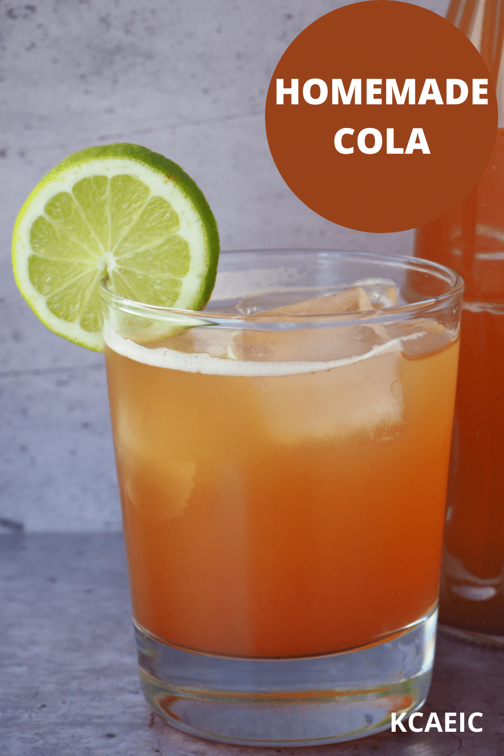 Glass of homemade cola with ice, lime circle garnish and bottle of cola beside it and text overlay, homemade cola, KCAEIC.