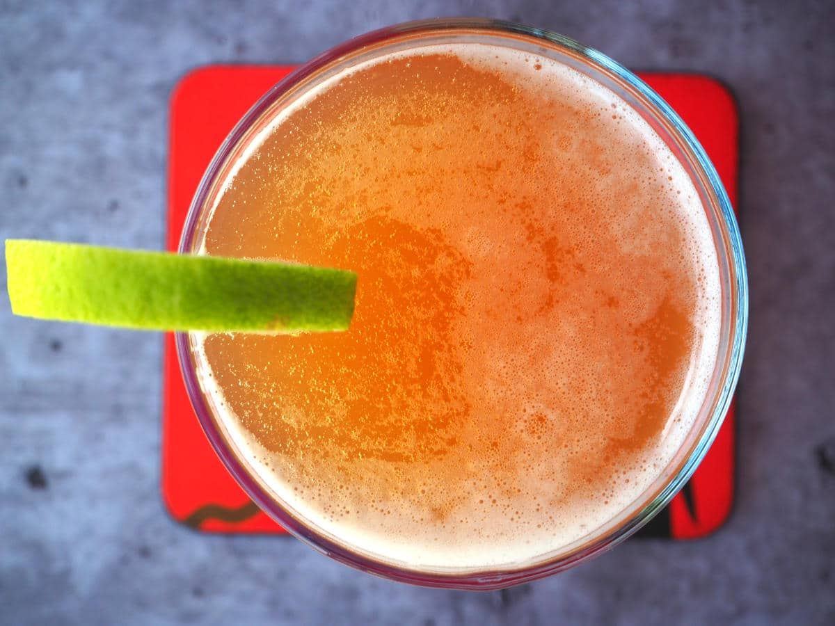 Top down view homemade cola in glass with lime circle garnish on side, with a red coaster under the glass.