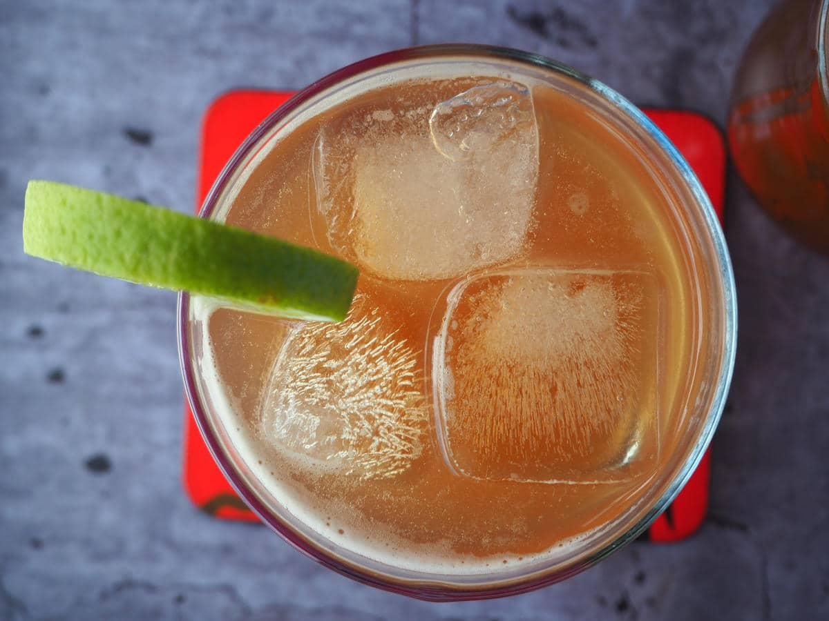 Top down view homemade cola in glass with lime circle garnish on side, red coaster underneath and bottle of cola next to it.