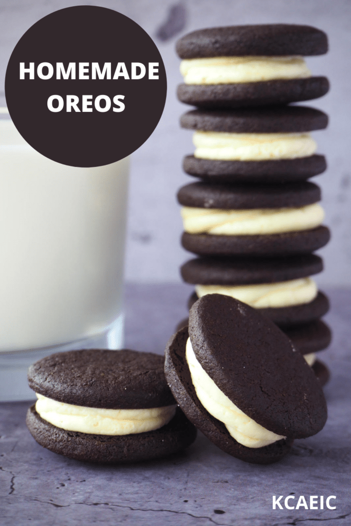 side view of stack of homemade oreos, with single oreo and one oreo propped on its side, with glass of milk and text overlay, homemade oreos and KCAEIC.