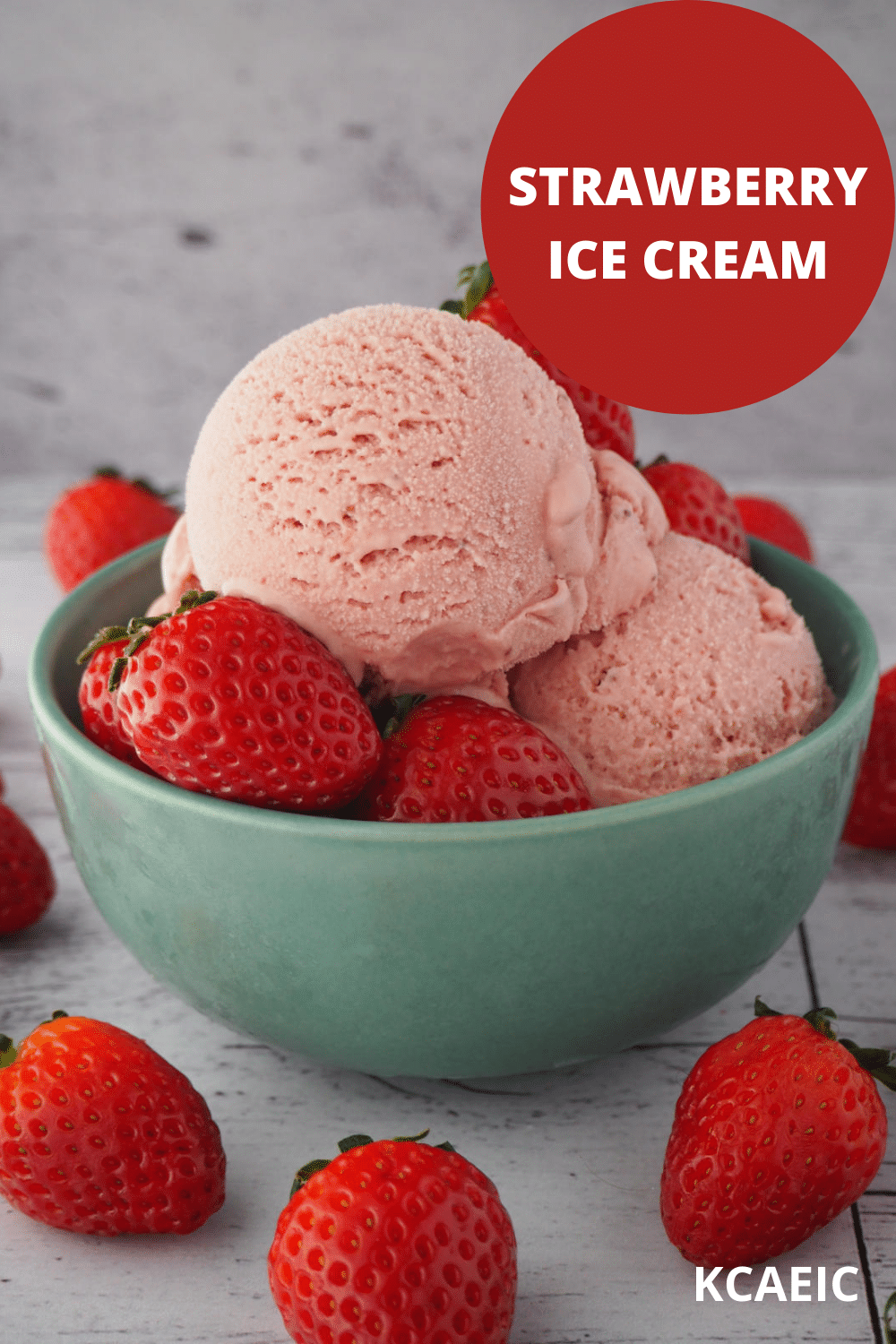 45 degree view of scoops of strawberry ice cream in a green bowl with strawberries in the bowl and strawberries scattered around it, on a white background, with text overlay, strawberry ice cream and KCAEIC.