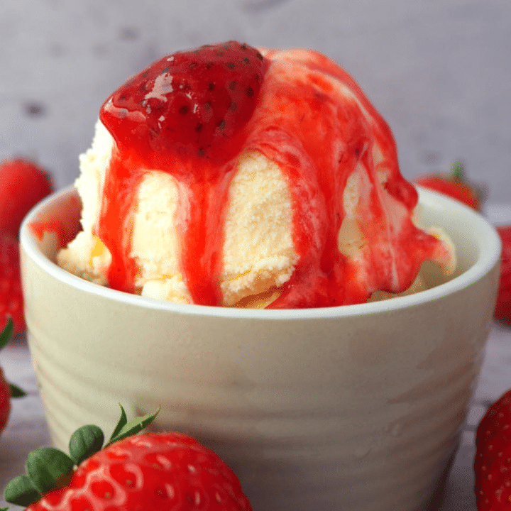 Close up side view of vanilla ice cream with strawberry and strawberry sauce, with strawberries scattered around, on a white floorboard surface