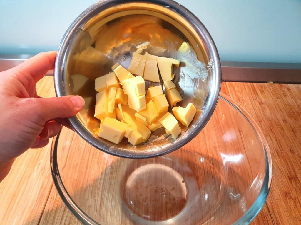 adding chopped room temperature butter to glass mixing bowl.