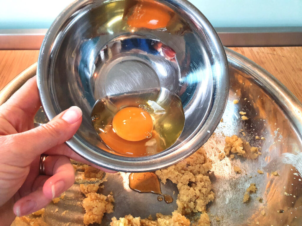 adding egg to butter, sugar and vanilla in a metal mixing bowl.