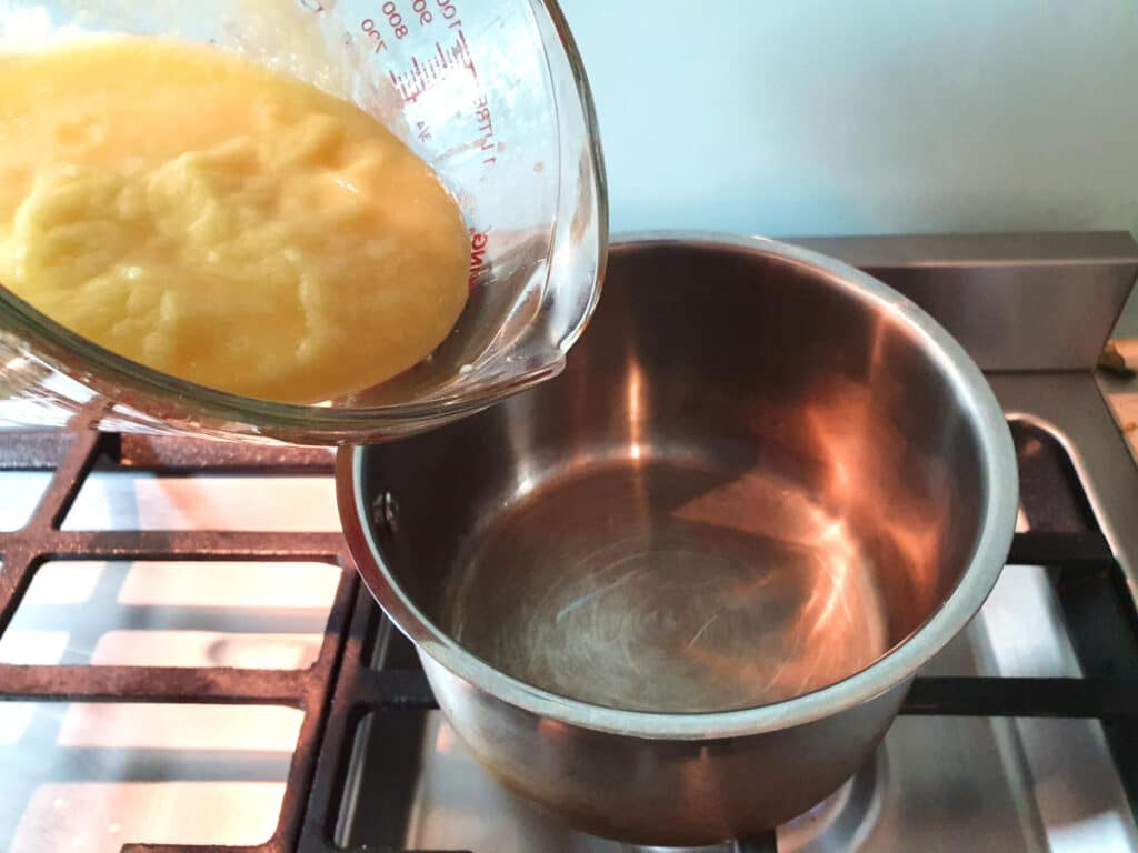 Adding blended pineapple to pot to reduce.