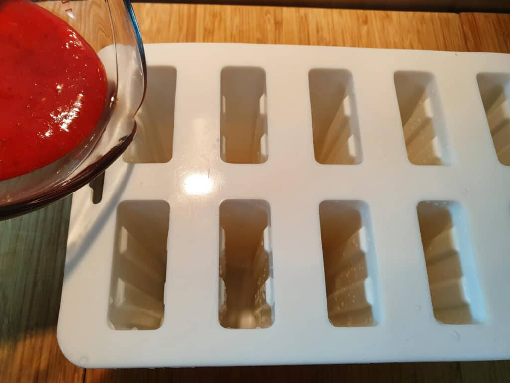 Add first layer of strawberry mix to popsicle molds.