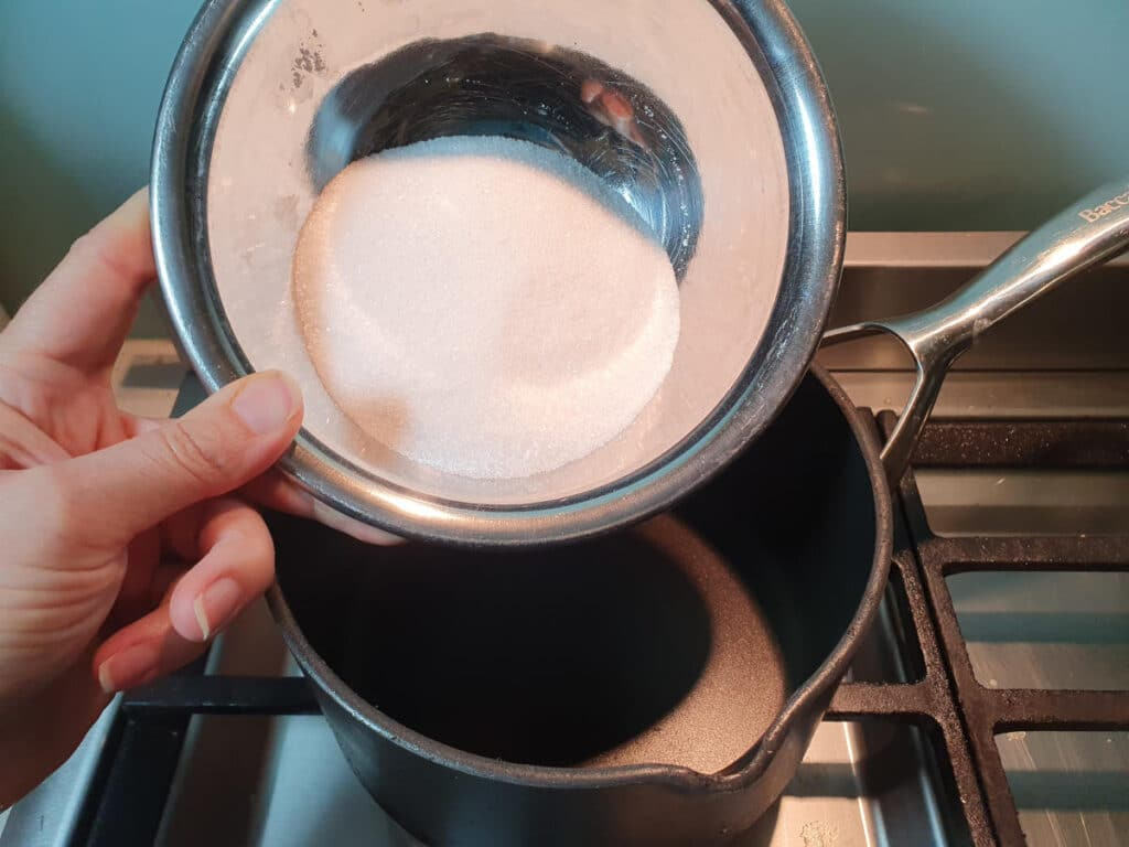 adding sugar to pot.
