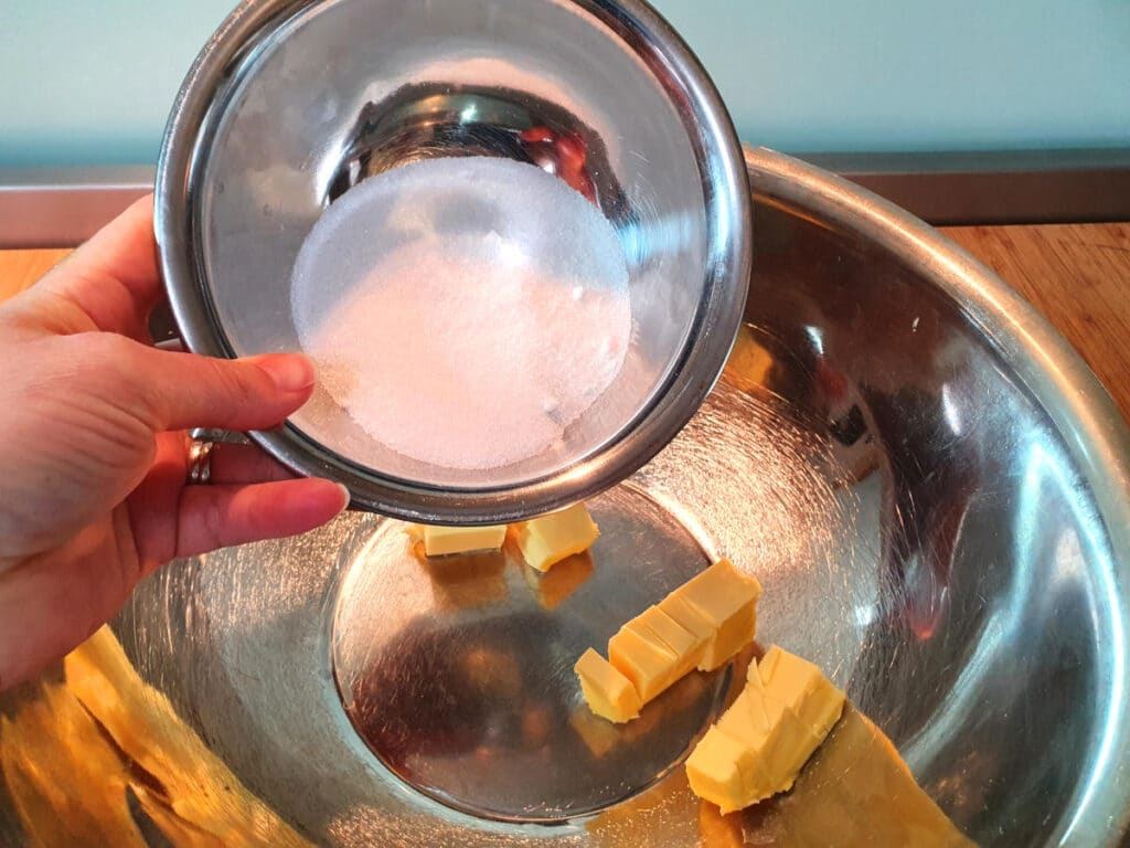 adding white sugar to butting in a large metal bowl.