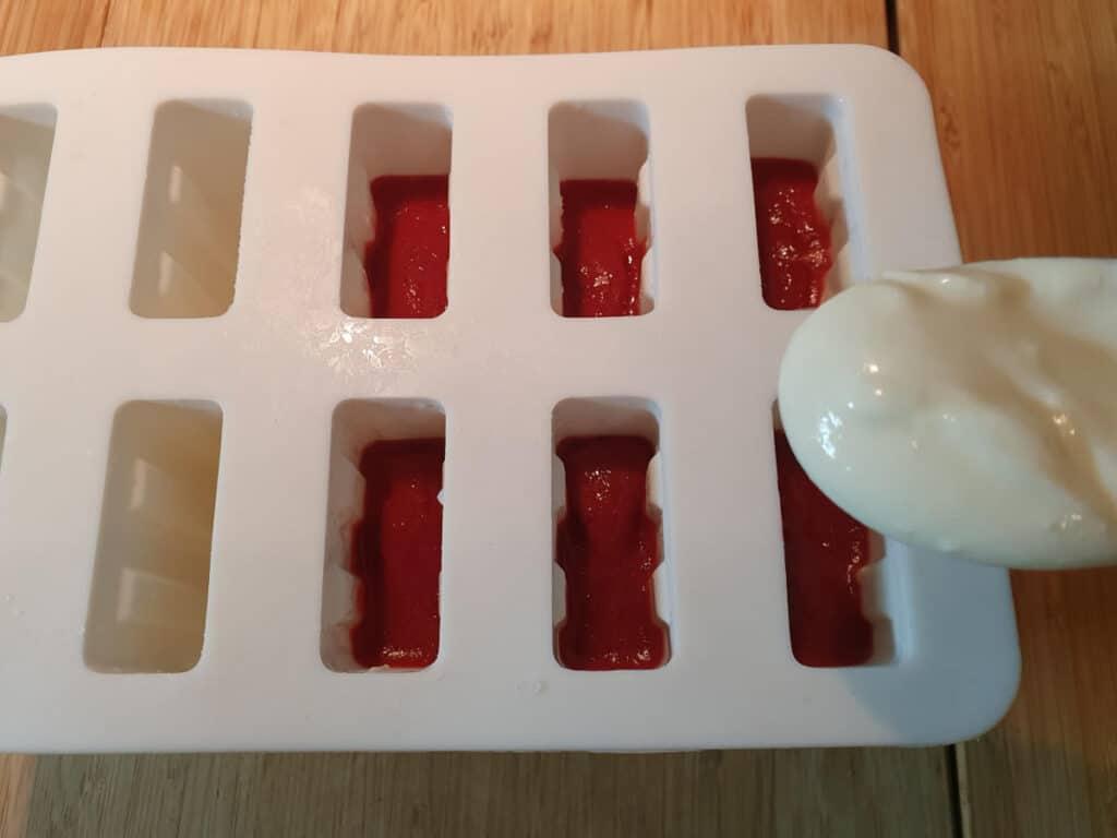adding top yogurt layer to popsicle molds.