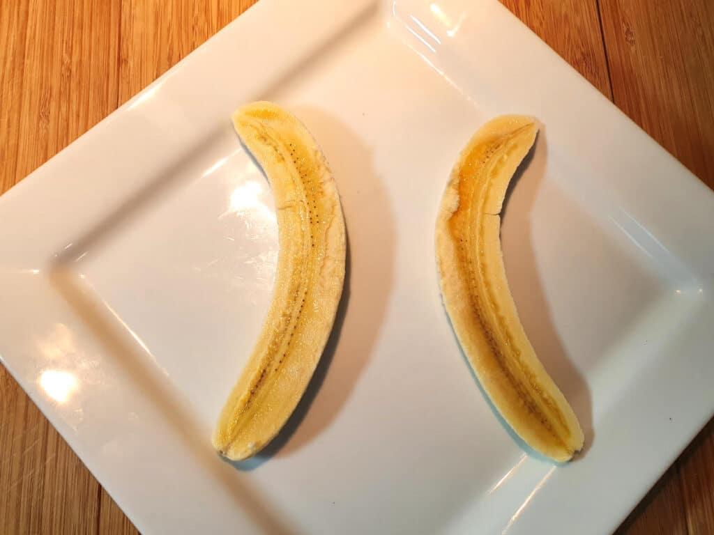 putting two banana pieces on plate, curves facing outwards, with space inbetween for the ice cream.