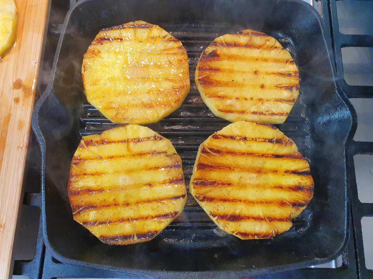 pineapple cooking in griddle pan showing cooked side of pineapple with griddle lines.
