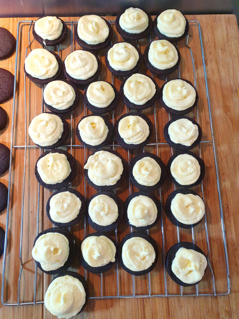 top down view cookies with vanilla filling on a wire rack, ready for cookies to place on top.