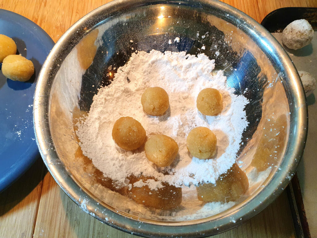 rolling multiple cookies in sifted icing sugar.