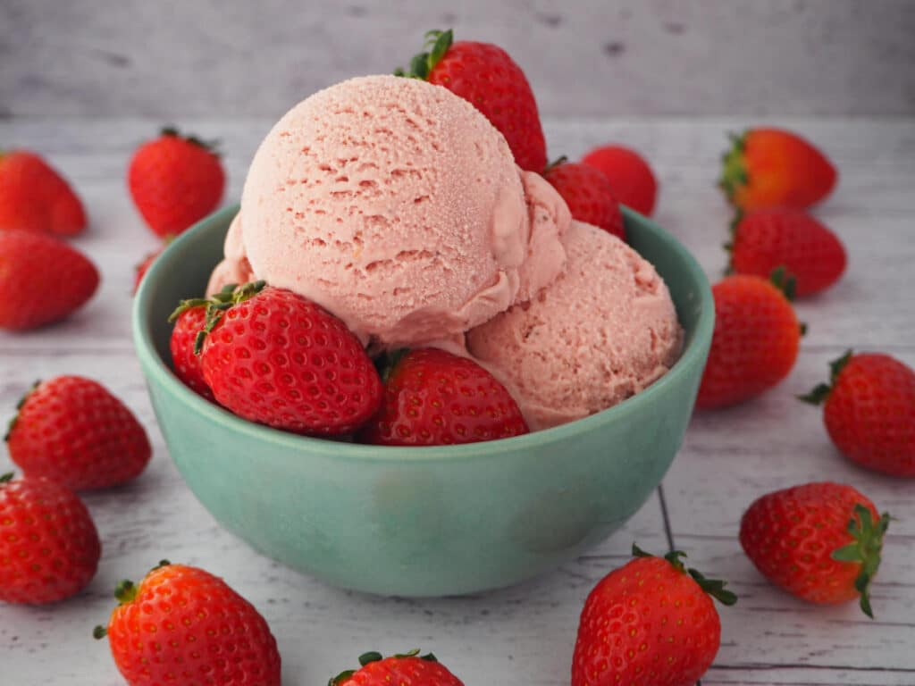 45 degree view of scoops of strawberry ice cream in a green bowl with strawberries in the bowl and strawberries scattered around it, on a white background.