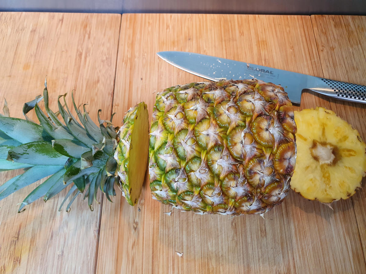 pineapple laid sidesways with the top and end cut off, with a large sharp knife, on a chopping board.