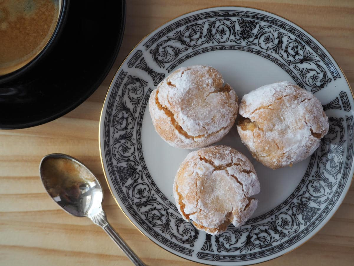 top down vew three amaretti cookies on a patterned plate, with cup of coffee and teaspoon on the side.