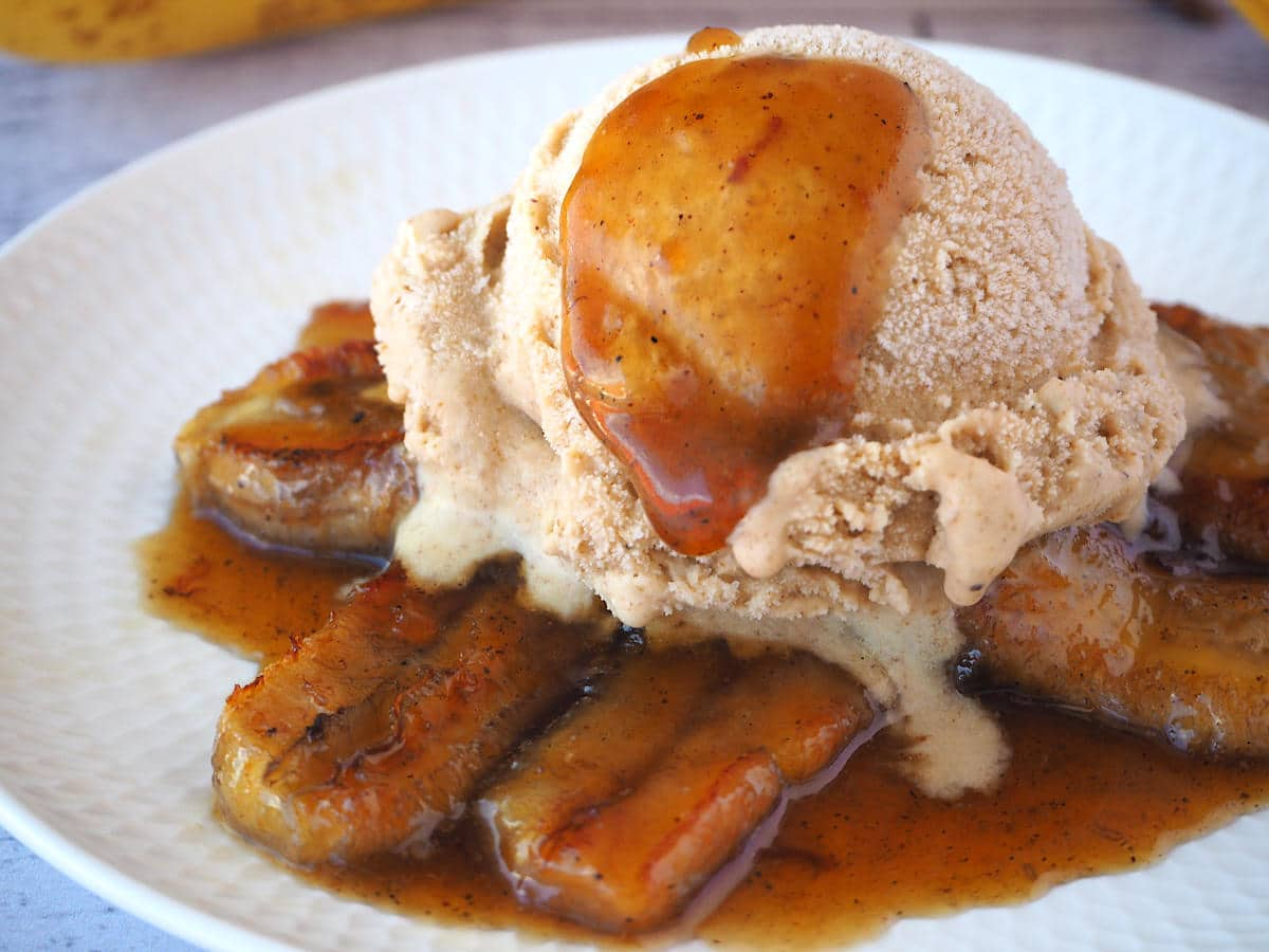 Caramelized bananas in caramel sauce, with a scoop of banana ice cream on top, and a spoon of caramel sauce dripping down the ice cream, on a white plate.