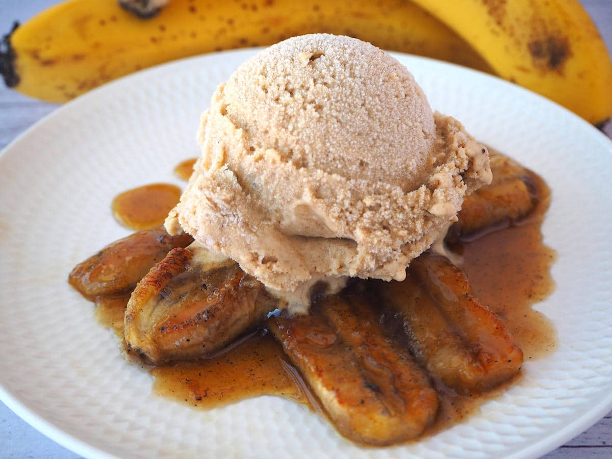 Caramelized bananas in caramel sauce, with a scoop of banana ice cream on top, on a white plate, with fresh bananas in the background.