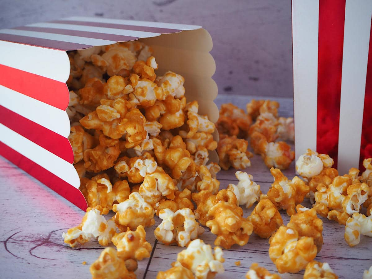 Red and white striped box of caramel popcorn tipped over with caramel popcorn scattered out and another red and white stripped box next to it.