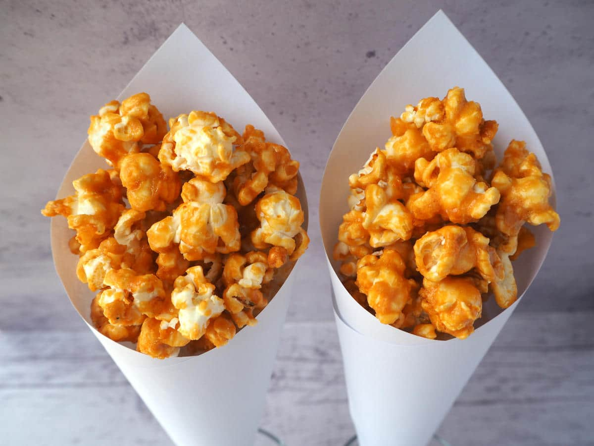 Two white paper cones of caramel popcorn.