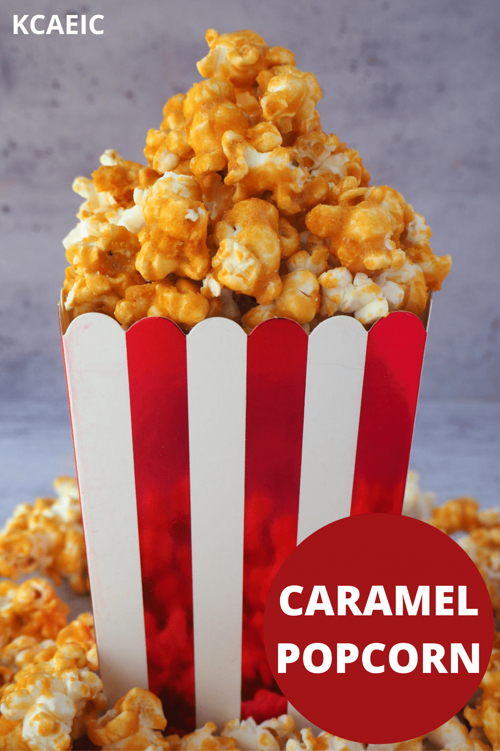 Caramel popcorn pilled in a red and white striped box, with caramel popcorn scattered around the bottom and text overlay, caramel popcorn and KCAEIC.