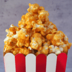 Close of up caramel popcorn pilled in a red and white striped box.