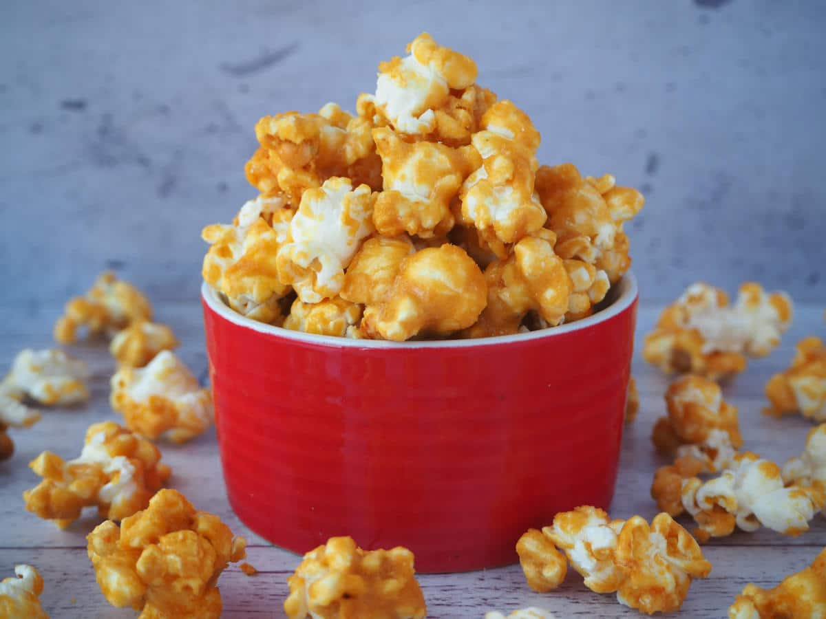 Caramel popcorn in a red bowl with caramel popcorn scattered around it.