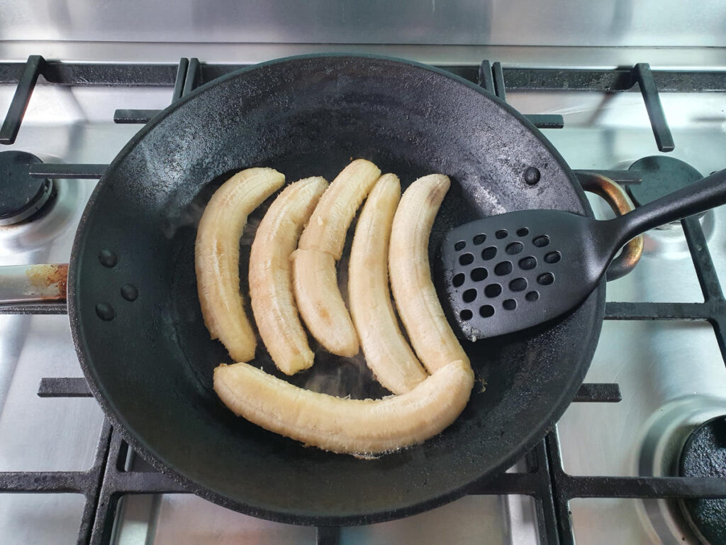 Flipping cooked bananas in frying pan with spatula.