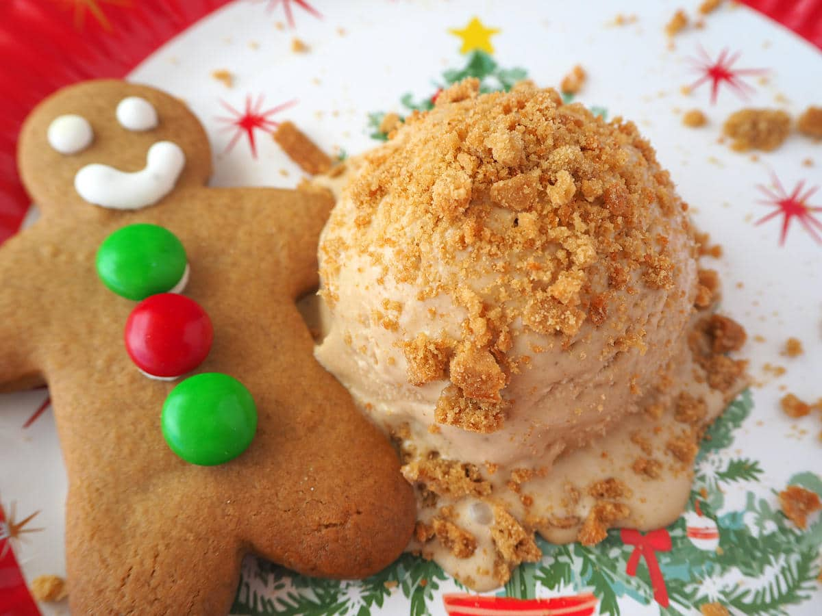 Scoop of gingerbread ice cream with crushed gingerbread on top, on a Christmas place, with a gingerbread man next to it.