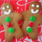 pair of decorated gingerbread med on a red Christmas serviette.