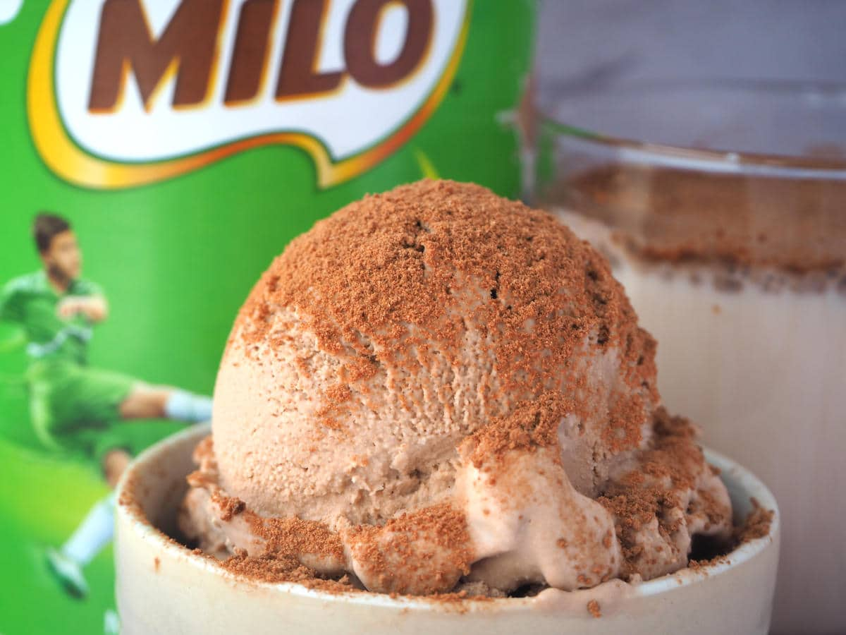 Close up scoop Milo ice cream sprinkled with Milo, in a small bowl, with Milo tin and glass of Milo in the background.
