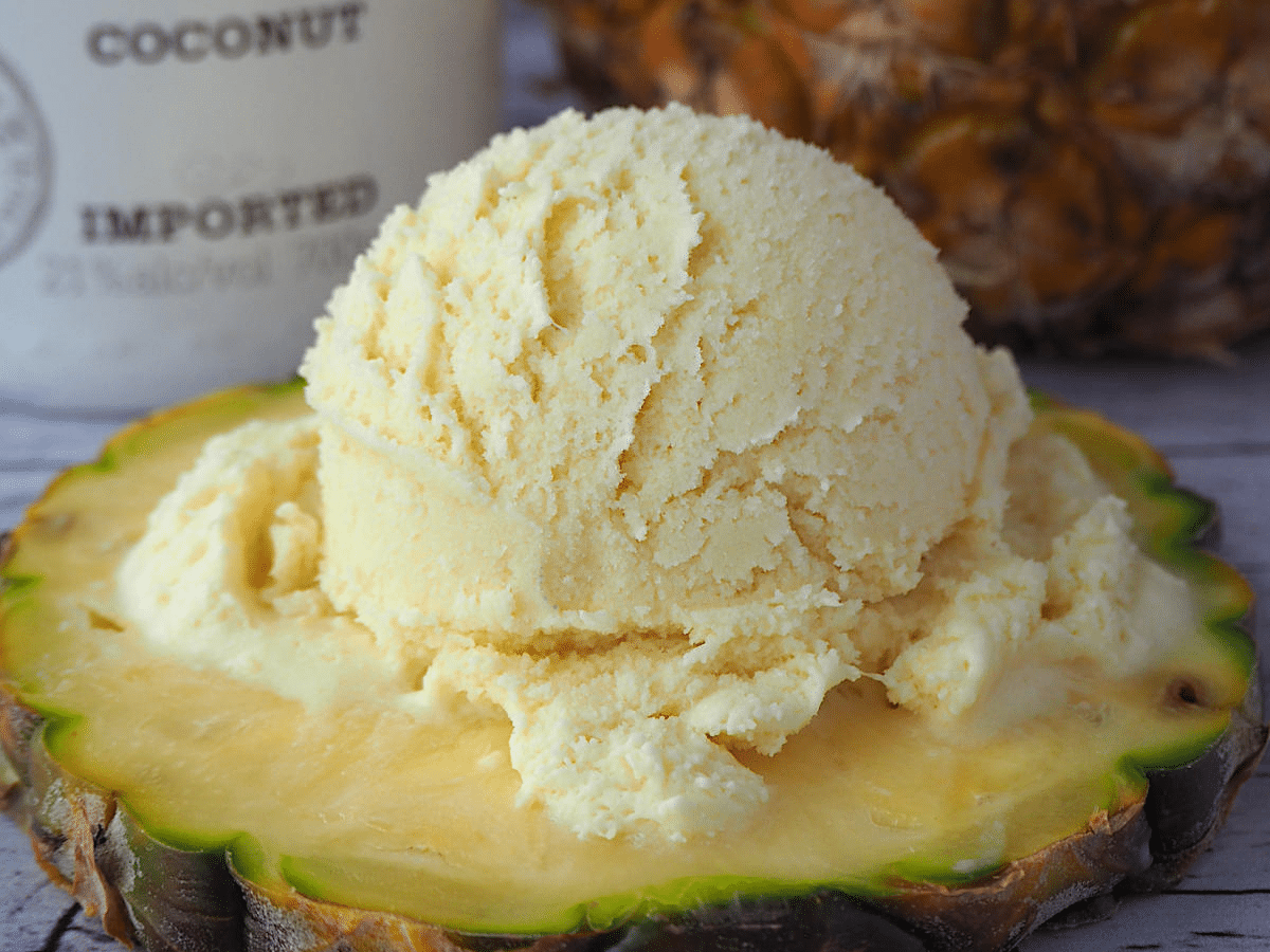 scoop of pina colada ice cream on pineapple slice, with coconut rum and pineapple in background.