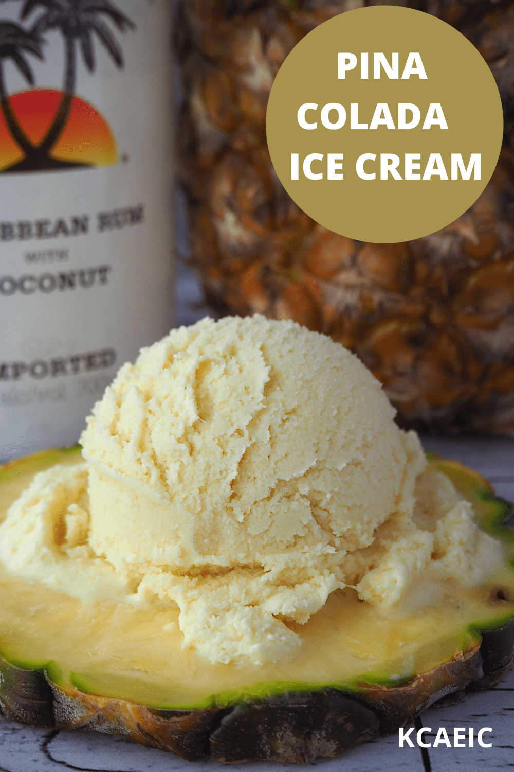 scoop of pina colada ice cream on pineapple slice, with coconut rum and pineapple in background, and text overlay, pina colada ice cream and KCAEIC.