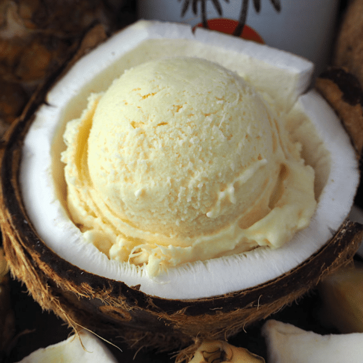 Scoop of pina cola ice cream in half a coconut, with pineapple and coconut rum bottle in background.