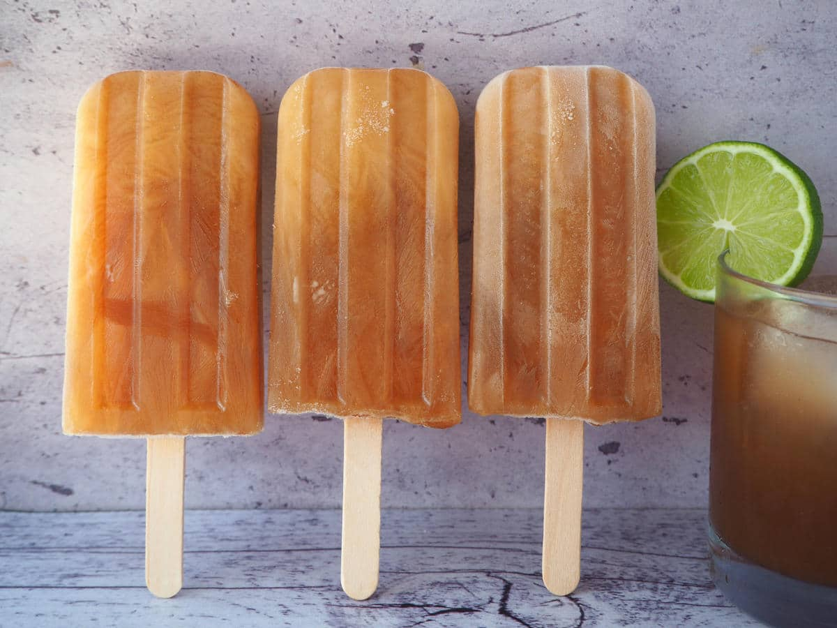 Row of three cola popsicles standing up next to a glass of homemade cola with a round lime garnish.